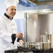 Smiling head chef stirring in pot — Stock Photo #36168309