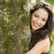 Stock Photo: Casual smiling brunette embracing tree looking at camera