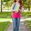 Stock Photo: Gorgeous smiling student carrying notebooks