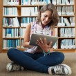 Female student against bookshelf using tablet PC on the library — Stock Photo #36168557