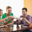 Four casual students drinking a cup of coffee — Stock Photo