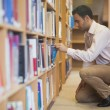 Handsome casual mcowering in front of bookshelves — Stock Photo #36168667
