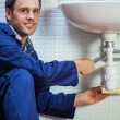 Handsome cheerful plumber repairing sink — Stock Photo
