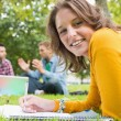 Female writing notes with students using laptop in park — Stock Photo #36168743
