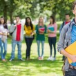 Stock Photo: College boy holding books with students in park