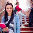 Female holding books with students on stairs in college — Stock Photo #36169061