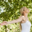 Attractive blonde woman practicing yoga in a park — Stock Photo