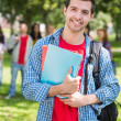 College boy holding books with blurred students in park — Stock Photo