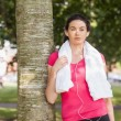 Young sporty woman leaning against a tree — Stock Photo