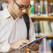 Mature student using tablet PC in the library — Stock Photo