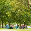 College students sitting on grass in park — Stock Photo