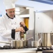 Stock Photo: Focused head chef flavoring food with pepper