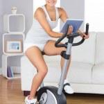 Happy training woman using an exercise bike — Stock Photo