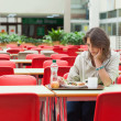 Stock Photo: Sad student sitting in cafeteriwith food tray