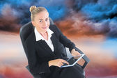 Composite image of businesswoman sitting on swivel chair with ta — Stock Photo