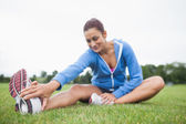 Woman stretching her leg while sitting on the grass — Stock Photo