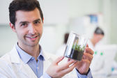 Smiling male researcher holding young plant at lab — Stock Photo