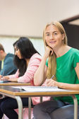 Student with others writing notes in classroom — Stock Photo