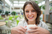 Smiling female student drinking coffee in the cafeteria — Stockfoto