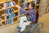 Man in wheelchair selecting book in the library — Stock Photo