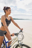 Smiling woman sitting on her bike on the beach — Stockfoto