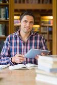 Feliz estudante maduro, segurando o tablet pc na biblioteca — Fotografia Stock
