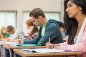 Young students writing notes in classroom — Stock Photo