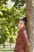Side view of attractive brunette woman leaning against a tree — Stock fotografie