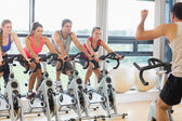 Man teaching spinning class to four people — Stok fotoğraf