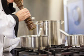 Head chef flavoring food with pepper — Stock Photo