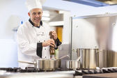 Smiling head chef flavoring food with pepper — Stock Photo