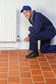 Happy handyman in blue coveralls repairing a radiator — Stock Photo