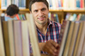 Mature student selecting book from shelf in the library — Stock Photo