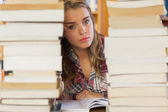 Stern pretty student studying between piles of books — Foto de Stock