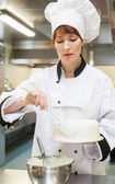Pretty focused head chef finishing a cake with icing — Stock Photo