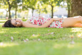 Stylish happy brunette lying on a lawn — Stock Photo