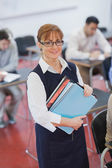 Pretty female teacher posing in her classroom holding some files — Stock Photo