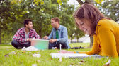 Student writing notes with males using laptop at park — Stock fotografie