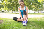 Active content brunette tying her shoelaces — Stock Photo