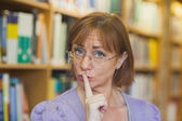 Female librarian giving a sign to be quiet standing in library — Stock Photo