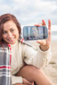 Woman self photographing with smartphone on beach — Stock Photo