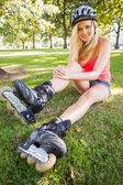 Casual gorgeous blonde wearing roller blades and helmet — Stock Photo
