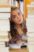 Unsmiling pretty student studying between piles of books — Stockfoto