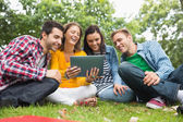 College students using tablet PC in park — Stok fotoğraf