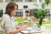 Student med mobiltelefon och bärbar dator vid cafeterian bord — Stockfoto