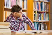 Handsome distracted student studying his books — Stock Photo