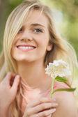 Femme blonde heureuse tenant une fleur blanche — Photo