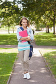 Pretty happy student carrying notebook — Stock Photo