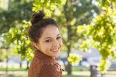 Cute brunette woman wearing a brown coat posing in a park — Stok fotoğraf