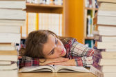 Tired pretty student resting head on table between piles of book — Stock Photo